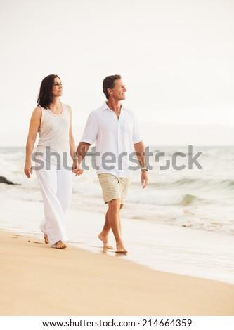 Mature Retired Couple Enjoying Sunset Walk on the Beach - stock photo