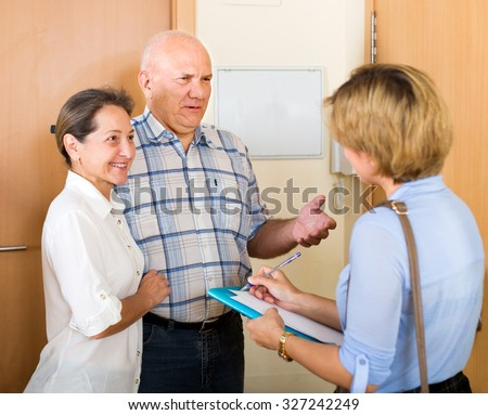 Mature 60s couple answering the questions of young employee  in door at home - stock photo