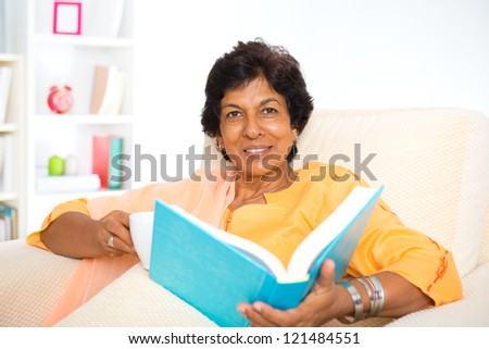 Mature 50s Indian woman reading a book at home - stock photo