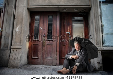 mature sad businessman seated in front of abandoned house - stock photo