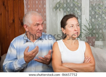 mature sad woman and man  in interior - stock photo