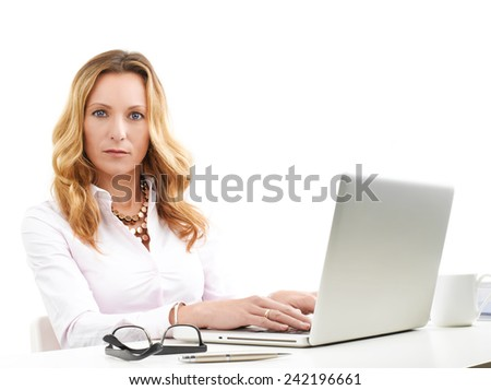 Mature sales woman typing on laptop while sitting at desk. Isolated on white background.  - stock photo
