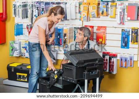 Mature salesman guiding female customer in selecting tools at hardware store