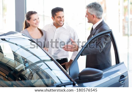mature salesman showing new car to a couple in showroom - stock photo