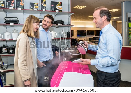 Mature salesman showing steam iron to young couple in hypermarket