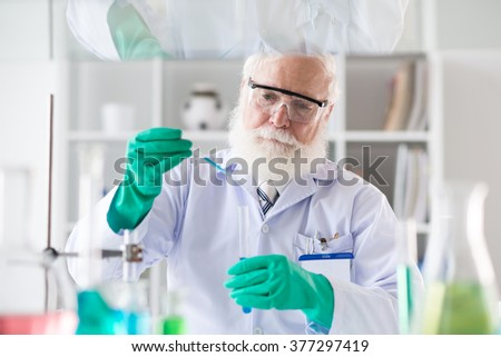 Mature scientist adding reagent into test-tube