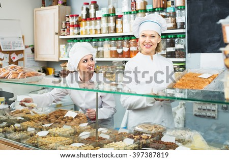 Mature seller and young assistant at confectionery display with pastry - stock photo
