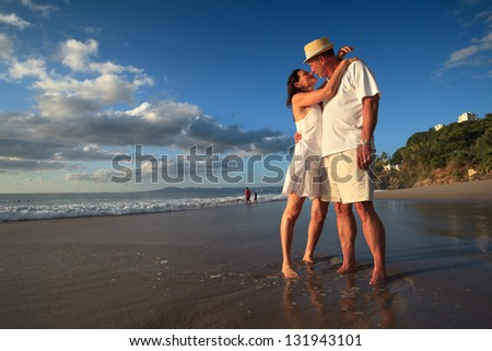 Mature senior adult couple kiss on tropical beach standing in ocean water. - stock photo