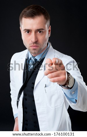 Mature Serious male doctor pointing finger at you isolated on black or dark grey background. Classic style in waistcoat with blue shirt and tie