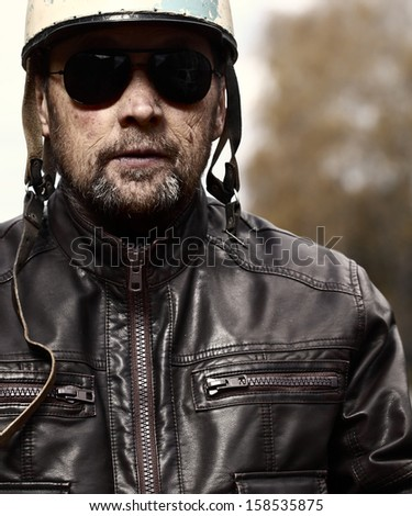 Mature serious man in a helmet and black glasses - stock photo