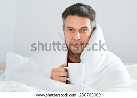Mature Sick Man Sitting On Bed Holding Cup Of Coffee - stock photo