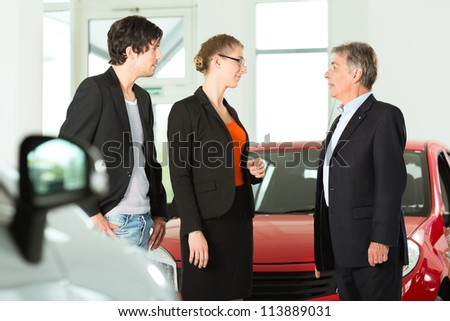 Mature single man with autos in light car dealership with a young couple, he obviously is buying a car or is a car dealer - stock photo