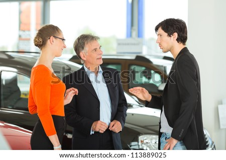 Mature single man with autos in light car dealership with a young couple,- man, young -, he obviously is buying a car or is a car dealer