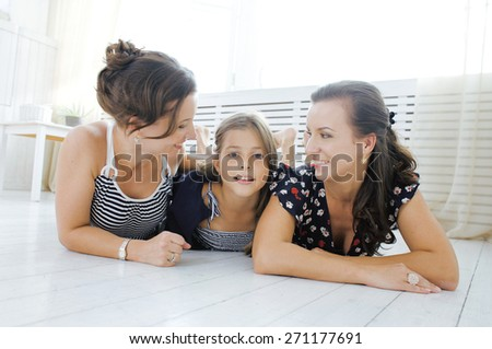 Mature sisters twins at home with little daughter, happy family smiling close up - stock photo