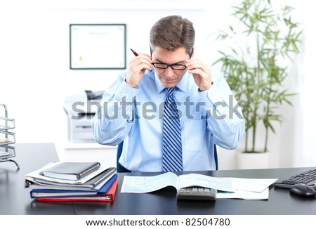 Mature smiling business man in modern office. - stock photo