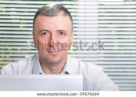 Mature smiling business man in office - stock photo