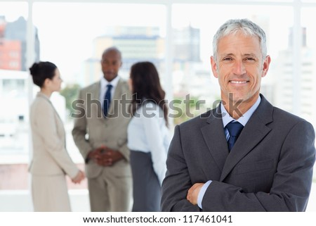 Mature smiling business manager crossing his arms in front of his business team - stock photo