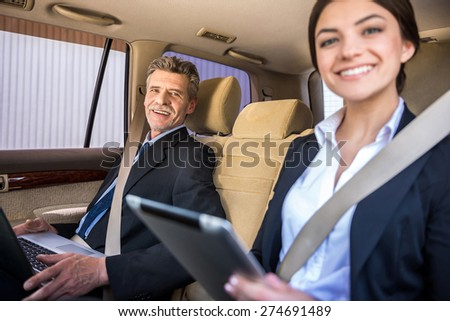 Mature smiling businessman in suit sitting in the car with his beautiful personal assistant and using his laptop. - stock photo