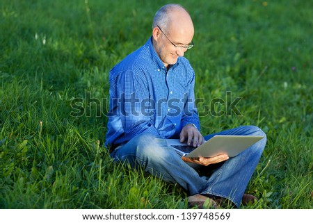 Mature smiling businessman using laptop while sitting on grass in park - stock photo