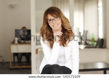 Mature smiling businesswoman sitting in her office - stock photo