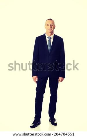 Mature smiling confident businessman standing. - stock photo