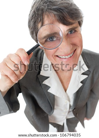 mature smiling lady looking through magnifying glass on white background - stock photo