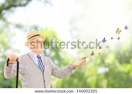 Mature smiling man holding a cane and looking at many colorful butterflies outside in a park - stock photo