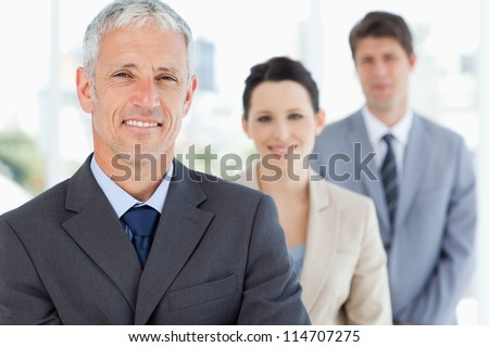 Mature smiling manager followed by two young business people - stock photo