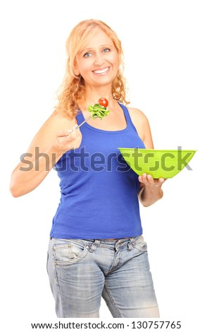 Mature smiling woman eating a salad isolated on white background - stock photo