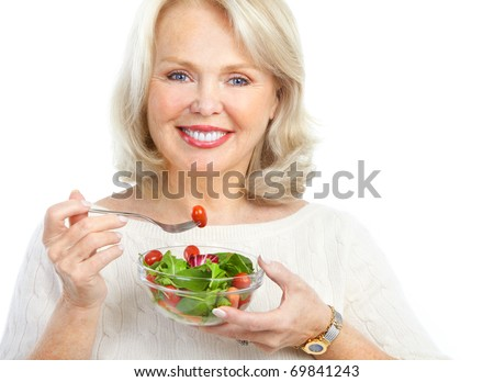 Mature smiling woman  eating salad,  fruits and vegetables.