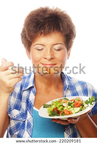 Mature smiling woman eating saladm isolated on white