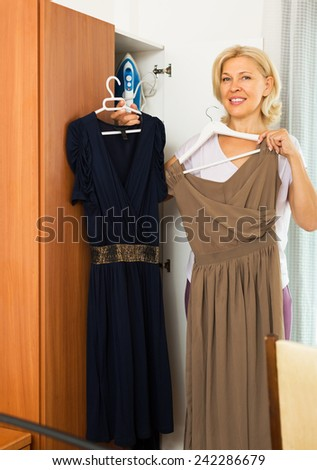 Mature smiling woman looking at clothes in closet - stock photo
