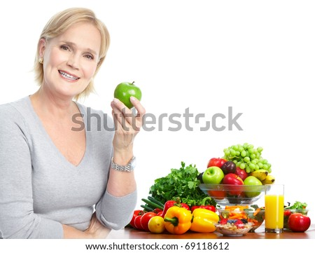 Mature smiling woman  with apple,  fruits and vegetables. - stock photo