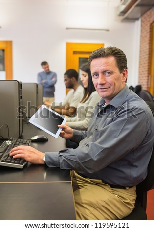 Mature student in computer class holding tablet pc in college - stock photo