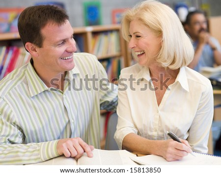 Mature student laughing with tutor in library - stock photo
