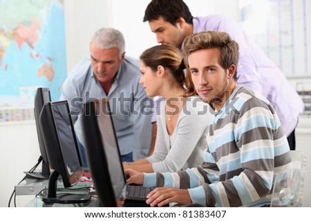 Mature students at computers - stock photo