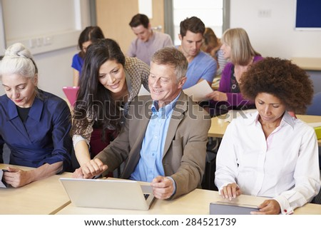 Mature Students In Further Education Class With Teacher - stock photo