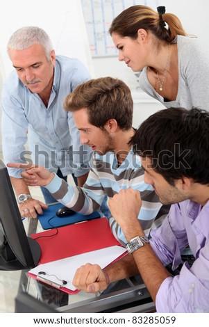 Mature students looking at a computer screen - stock photo