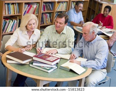 Mature students studying together in library - stock photo