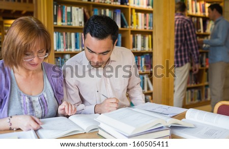 Mature students studying together while two men at bookshelf in the library - stock photo
