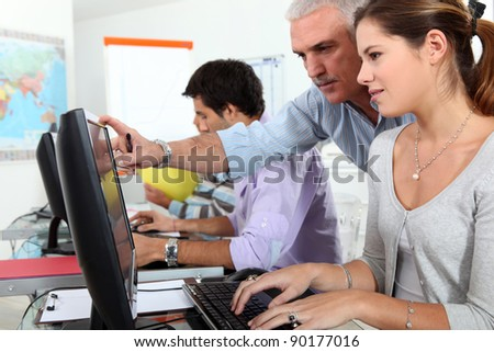 Mature students using computers in a classroom - stock photo