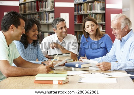 Mature students working in library - stock photo