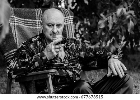 Mature stylish man tasting a glass of red wine, traditional red plaid at autumn . Alone seniors smelling a glass of red wine. Thinking about life and problems with wine