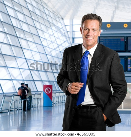 Mature successful businessman smiling and looking at camera in a modern airport - stock photo