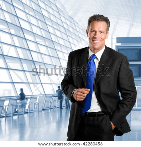 Mature successful businessman smiling and looking at camera in a modern office building - stock photo