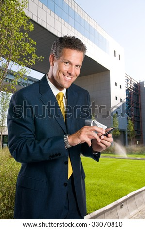 Mature successful businessman text messaging on mobile outdoor in a business park - stock photo