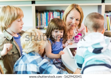 Mature teacher with elementary students using digital tablet in library - stock photo