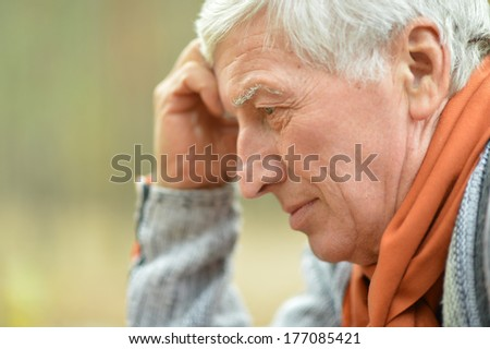 Mature thoughtful man outdoors over autumn background