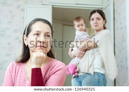 Mature thoughtful woman against her adult  daughter with little baby  at home - stock photo