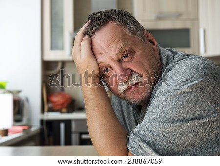 Mature tired man sitting at a table in his apartment - stock photo